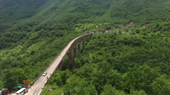 Flying over Tara river canyon with Durdevica arch bridge. National park Durmitor Stock Footage