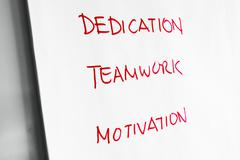 Dedication, Teamwork and Motivation words on paper - stock photo