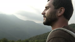 Young beautiful beard man on mountain with a red vintage backpack Stock Footage