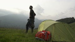 Young beautiful beard man on mountain is watching panorama near his tent Stock Footage