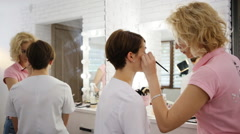 Young makeup artist applying make up near professional fashion studio mirror Stock Footage