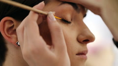 Close up of female arm of makeup artist holding eyeliner and applying it on eye Stock Footage