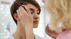 Makeup artist applying brow shadow on beautiful young woman with short haircut - stock footage