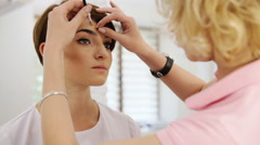 Beautiful woman drawing a shape of eyebrows using eyebrow pencil. Make up artist Stock Footage