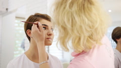 Professional make up artist applying with brush cosmetic on eyebrow of fashion Stock Footage