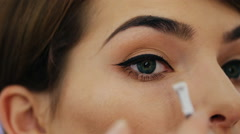 Close-up of of a beautiful young woman with esthetician making makeup applying Stock Footage