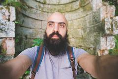 Bearded man posing against old brick wall, Garda, Italy - stock photo