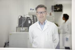 Scientist smiling in laboratory, colleague working in background - stock photo