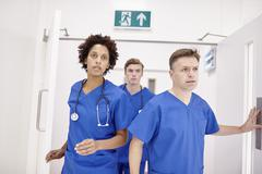 Doctors running into emergency room in hospital - stock photo
