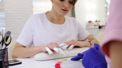 Beautiful brunette client in salon choosing color for gel manicure with nails Stock Footage