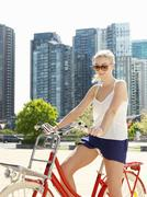 Young woman on bicycle, Southbank, Melbourne, Australia - stock photo
