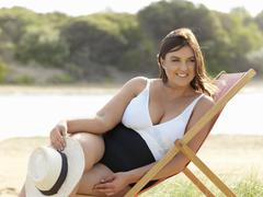Woman in swimsuit sitting on beach chair, Point Impossible, Victoria, Australia - stock photo