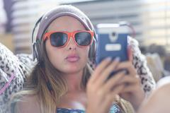 Teenager with sun glasses using smartphone on lazy chair Stock Photos