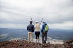 Three friends standing at the summit of South Sister volcano, looking at view, Stock Photos