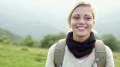 Young beautiful blonde woman is walking outdoor on mountain Stock Footage