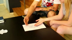 Woman consults with master of a tattoo in the studio tattoo Stock Footage