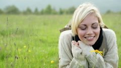 Young beautiful blonde woman lie down on grass on mountain portrait Stock Footage