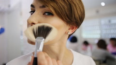 Attractivesmiling woman applying make up to her face with a brush looking at Stock Footage