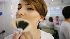 Funny woman plays with makeup brush looking at camera. Creative make up artist Stock Footage