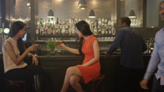 4K Female friends chatting & drinking cocktails in trendy city bar Stock Footage