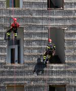 bold and daring climbers of firefighters climbing a wall of a house during th - stock photo