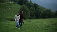 Young beautiful romantic couple is walking outdoor on mountain - stock footage