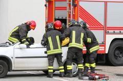 brave firefighters relieve an injured after car accident - stock photo