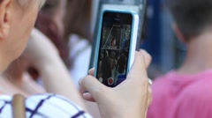Spectator holding smart phone shooting video for social media of music concert Stock Footage