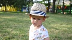 Cute little kid boy in hat portrait walking in park slow motion Stock Footage