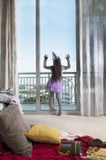 Young girl, wearing party clothes, looking out of window, rear view - stock photo