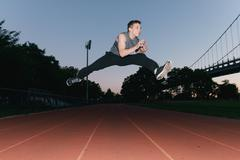 Young man jumping, mid air, on race track, sunset, low angle view Stock Photos