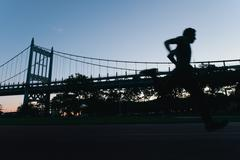 Young man running on race track, sunset, low angle view Kuvituskuvat