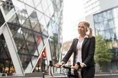 Businesswoman with bike outside 30 St Mary Axe, London, UK - stock photo