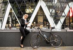 Businesswoman with bike outside 30 St Mary Axe, London, UK Stock Photos
