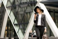 Woman texting while walking, 30 St Mary Axe in background, London, UK Stock Photos