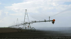 Sprinkler irrigation system is sprinkling water in a field - stock footage