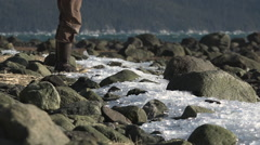 Man In Rubber Boots Stepping Into Frame At Rocky Icy Beach Stock Footage