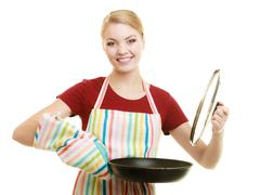 Housewife or chef in kitchen apron with skillet frying pan Stock Photos