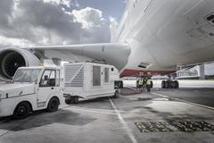 Ground crew operating loading equipment on A380 aircraft - stock photo
