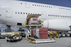Ground crew loading freight and luggage into A380 aircraft - stock photo
