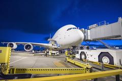 A380 aircraft on stand at airport at night - stock photo