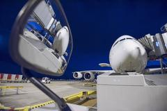 Night over A380 aircraft on stand at airport, reflected in wing mirror of ground - stock photo