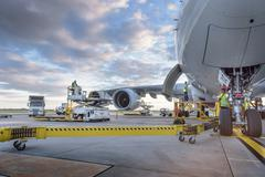 Ground crew attending to A380 aircraft at airport - stock photo