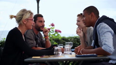 Four multiethnic friends are having fun chattering at italian restaurant Stock Footage
