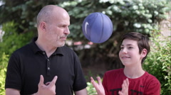 Father and son sitting next to each other bouncing ball - stock footage