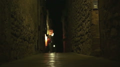 Four multiethnic friends are walking at night in an old town centre alley Stock Footage
