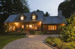 Reconstructed 1976 cottage style log home facade at dusk, Quebec, Canada Stock Photos