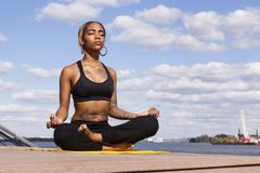 Young woman sitting cross legged by water in yoga position, eyes closed, - stock photo