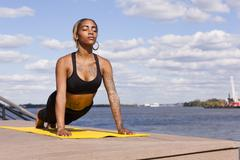 Young woman resting on hands by water in yoga position, eyes closed, - stock photo