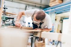 Young man in workshop looking down counting plywood sheets Stock Photos